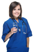 Attractive young nurse with a stethoscope. Holding a glass of mi — Stock Photo