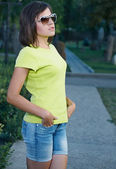 Attractive young woman in a yellow shirt and sunglasses. — Stock Photo