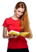 Attraktiv ung kvinna i en röd tröja. läser en gul bok. — Stockfoto