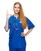 Attractive young nurse in uniform. Shows sign okay. Isolated on — Stock Photo