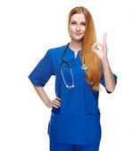 Attractive young nurse in uniform. Shows sign okay. — Stock Photo