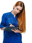 Attractive young nurse in uniform. Holds a folder and write. Iso — Stock Photo