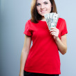 Stock Photo: Attractive young woman in a red shirt. Holding money.