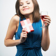 Happy young woman in a blue dress. Holding red gift box and glas — Stock Photo #42333489