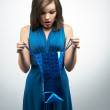 Surprised young woman in a blue dress. Holding gift bag. — Stock Photo #42333641