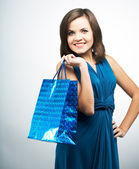 Attractive young woman in a blue dress. Holds a gift bag.  — Stockfoto