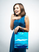 Surprised young woman in a blue dress. Holding gift bag.  — Stock Photo
