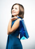 Smiling young woman in a blue dress. Holding gift bag and lookin — Stock Photo