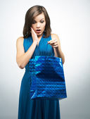 Surprised young woman in a blue dress. Holding gift bag.  — Foto de Stock