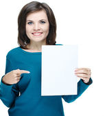 Attractive young woman in a blue shirt. Holds a poster and point — Stock Photo