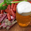 Mug of beer and an assortment of salami and vegetables on a cutt - Stock Photo
