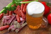 Mug of beer and an assortment of salami and vegetables on a cutt — Foto de Stock