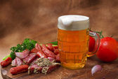 Still life with beer and salami — Stock Photo