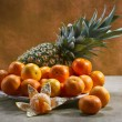 Stock Photo: Still life with tangerines and pineapple