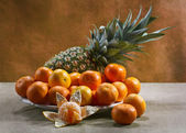 Still life with tangerines and pineapple — Stock Photo