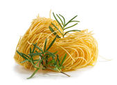 Vermicelli pasta nests with rosemary on a white background — Stock Photo