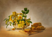 Still life with yellow flowers and a cake — Stock Photo