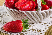 Ripe strawberries in ceramic basket on wooden background — Stock Photo