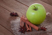 Apple with anise and cinnamon on wooden background — Stock Photo