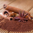 Ground coffee with cinnamon and star anise on a wooden backgroun — Stock Photo