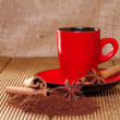 Coffee in a red cup with cinnamon and anise stars. — Stock Photo