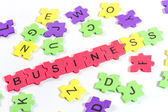 Word BUSINESS formed with colorful foam puzzle on white backgro — Stock Photo