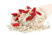 овсяное зерно отслаивается с goji ягодами на белом фоне — Стоковое фото