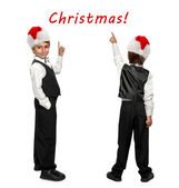 Little boy in a tuxedo and  in Santa Claus xmas red hat pointing — Stock Photo