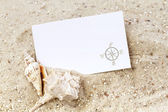 Seashells with blank card on a sandy background — Stock Photo