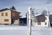 Football pitch and deserted village during the winter — Stock Photo