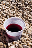 Plastic cup with red liquid — Stock Photo