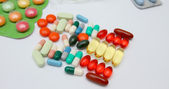 Multi coloured pills on white background — Stock Photo