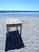 Old wooden table abandoned on a beach — Stock Photo