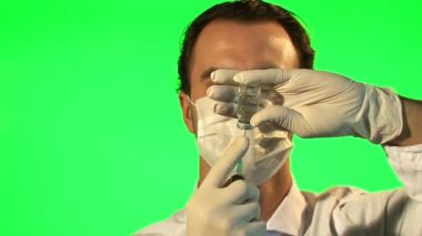 Doctor with syringe drawing up clear liquid form bottle — Stock Video