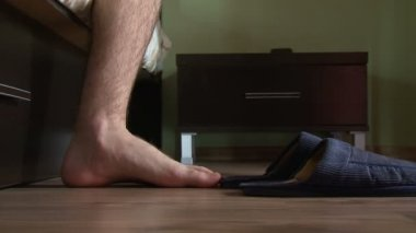Male feet getting out of bed, put on slippers — Stockvideo