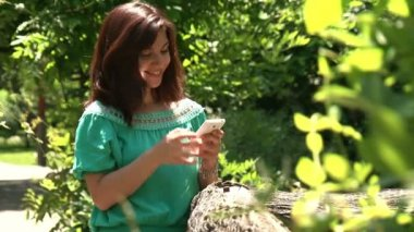 Girl texting in a park — Stockvideo