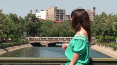 Girl standing on a bridge, looking at the river — Stock Video