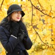 Woman in a black hat on background of autumn tree — Stock Photo