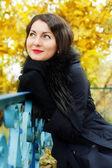 Beautiful woman sitting near the old railing — Stock Photo