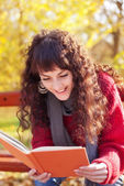 Girl reading a book in autumn park — Stock Photo