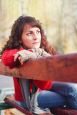 Sad girl in a park on bench — Stock Photo