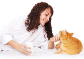 Girl with a cup of coffee and her cat in bed — Stockfoto