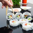 Hand holding stick with maki sushi set - Stock Photo