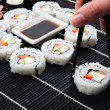 Woman's hand taking philadelphia sushi. Black mat in background — Stock Photo