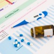 Foto Stock: Electronic thermometer and pills on fertility chart