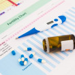 Stock Photo: Electronic thermometer and pills on fertility chart