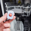 Royalty-Free Stock Photo: Hand holding dishwashing tablet. Dishwasher in background