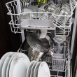 Dishwasher with white plates and glasses - Stock Photo