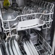 Dishwasher with white plates - Stock Photo