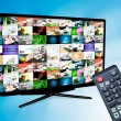 Royalty-Free Stock Photo: TV with multiple images gallery on blue background. Hand hold re